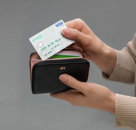 Kuvassa henkilö asettaa Oma Säästöpankin maksukorttia lompakkoon.