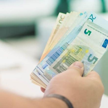 Kuvassa on suomalaisia seteleitä henkilön kädessä