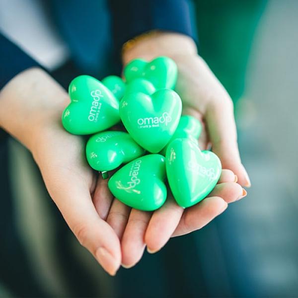 Kuvassa on OmaSp:n vihreitä sydämiä kädessä